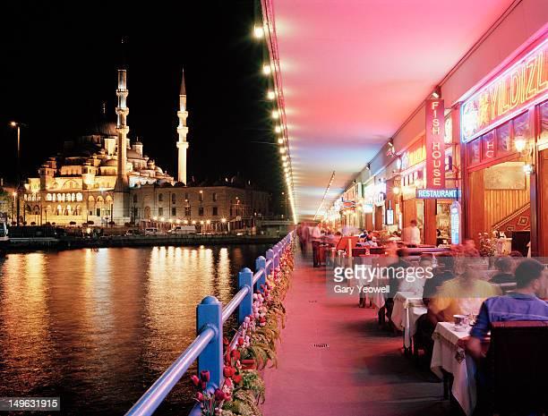 tourists dining along galata bridge at night - istanbul stock-fotos und bilder