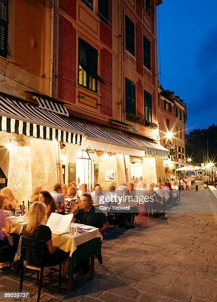 tourists dining along restuarants at dusk - genoa italy stock pictures, royalty-free photos & images