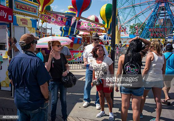 Tourists discuss buying tickets for rides in Luna Park along the boardwalk July 24 2015 at Coney Island Beach in the Brooklyn borough of New York