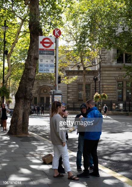 los turistas discutiendo planes en lugar de san martín, londres de viaje - avenida fotografías e imágenes de stock