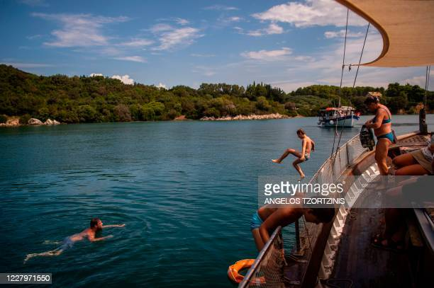 Tourists dive from a boat and swim during a dolphin watching tour in the Amvrakikos gulf, in Preveza, northwestern Greece, on August 6, 2020. - Based...