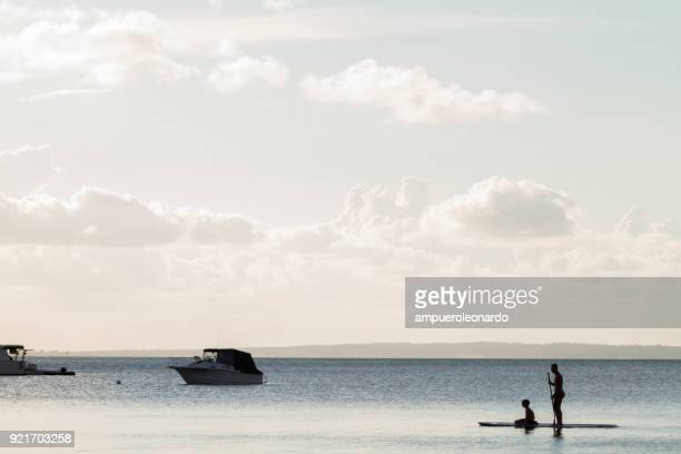 tourists doing paddle boarding in a calm ocean in fraser island, queensland, australia - seascape stock pictures, royalty-free photos & images