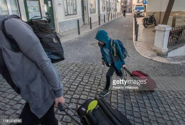Tourists drag their luggage uphill in Calçada Salvador Correia de Sa Santa Catarina historical neighborhood on October 15 2019 in Lisbon Portugal...