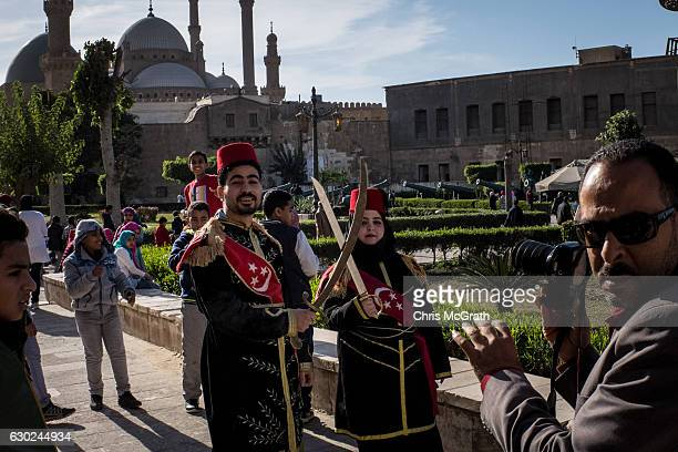 Tourists dress up for a photograph at a tourist attraction on December 16 2016 in Cairo Egypt Since the 2011 Arab Spring Egyptians have been facing a...