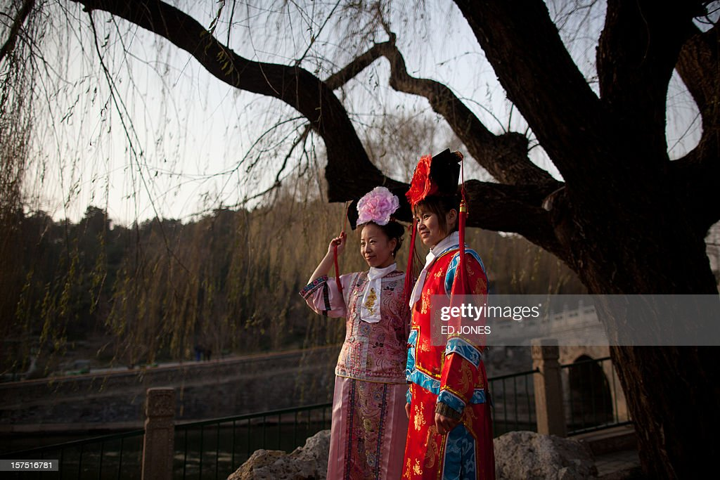 Tourists dressed in Qing dynasty style clothing pose for their friends in Beihai park in Beijing on December 4, 2012. The latest batch of purchasing managers' indexes from HSBC show manufacturing activity in China hit a 13-month high, while India also saw its strongest expansion since June. AFP PHOTO / Ed Jones