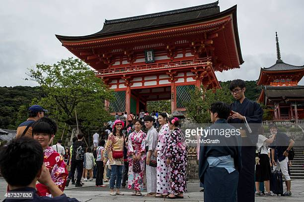 Tourists dressed in traditional Japanese outfits pose for photographs in front of the Kiyomizu Temple on September 7 2015 in Kyoto Japan The famous...
