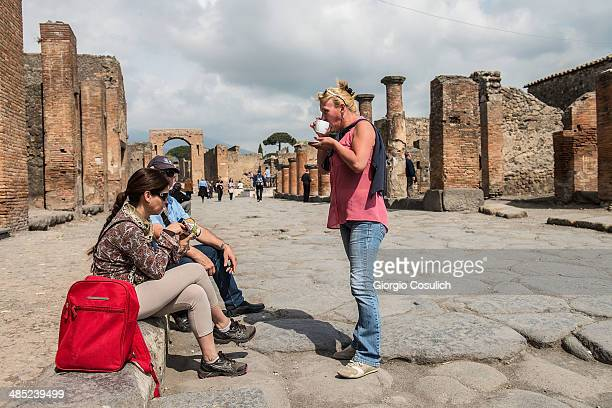 Tourists drink a coffee as they visit the ruins at the archaeological site on April 12 2014 in Pompei Italy The Italian government has enacted a...