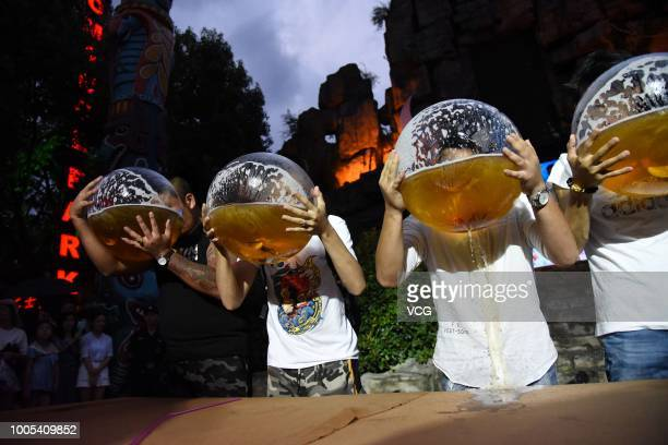 Tourists drink beer with fishbowls during a beer drinking competition at Song Dynasty Town on July 21 2018 in Hangzhou Zhejiang Province of China