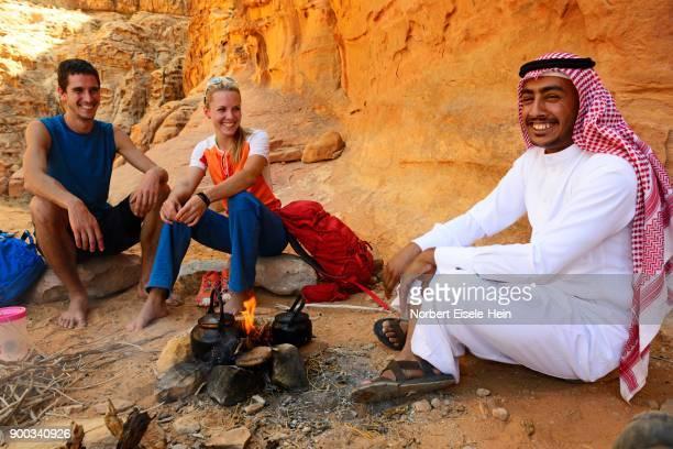 tourists drink tea with bedouin in wadi rum, jordan - bedouin stock pictures, royalty-free photos & images