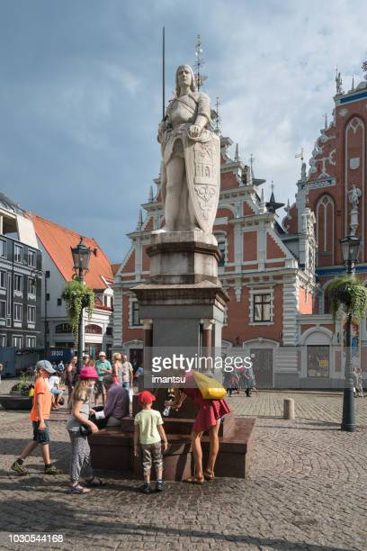 tourists  drinking water in the old town square, next to statue of roland  and blackheads house - blackheads stock photos and pictures