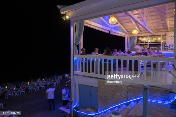 Tourists eat and drink in a restaurant by the sea in Hersonissos, on the island of Crete, Greece, on Tuesday, Sept. 24, 2019. Like Crete, Europes...