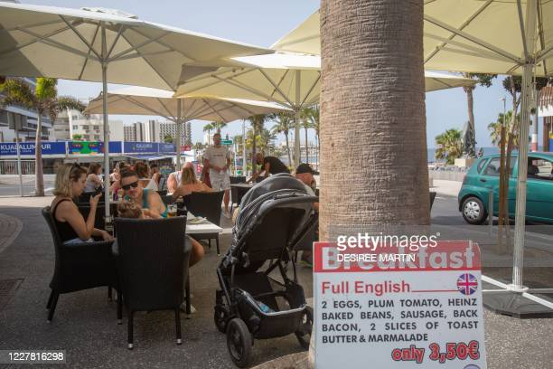 Tourists eat at a restaurant at the Playa de Las Amaricas on the Canary Island of Tenerife on July 28, 2020. - After Britain's quarantine move and a...