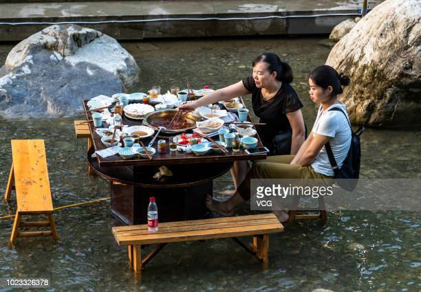 Tourists eat hot pots in water to cool off at a scenic spot of Mount Jinfo on August 21 2018 in Chongqing China According to China Meteorological...