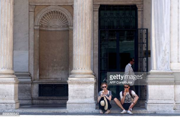 Tourists eat ice-creams in the shade on June 22, 2017 in central Rome during a hot summer-day. In Italy, forecasters say the current heatwave could...