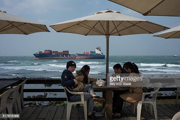 Tourists eat in a seaside cafe near a coastal area affected by the oil spill near Taiwan's north coast on March 26, 2016 in Shihmen, Taiwan. An oil...