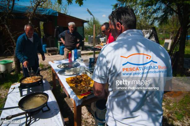 Tourists eat 'Moeche' after a fishing tour organized by Cooperativa San Marco in Burano on April 14 2018 in Venice Italy At the beginning of the...