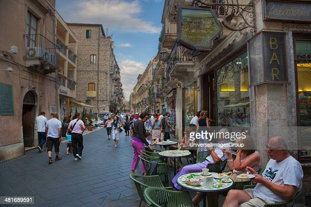 Tourists eating food at a sidewalk cafe on the street Taormina Sicily Italy