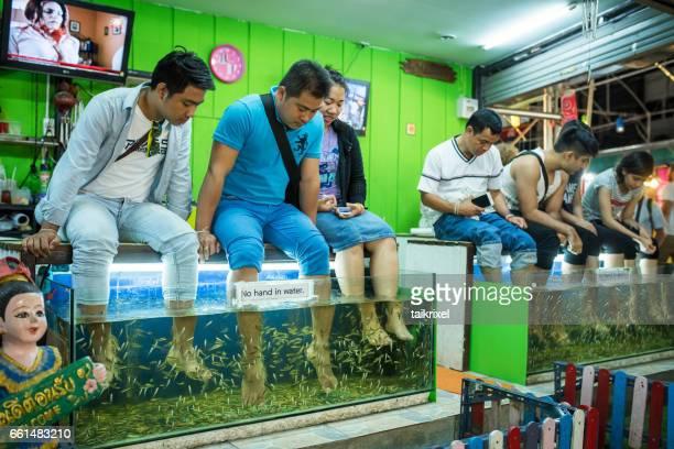 os turistas desfrutar de um banho com médico peixes, chiang mai, tailândia - símbolo conceitual - fotografias e filmes do acervo