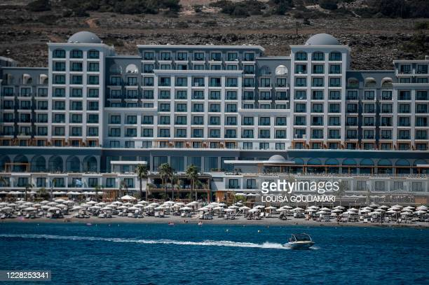 Tourists enjoy a beach in front of a hotel on the Aegean island of Rhodes on August 29, 2020. - Rhodes island, one of the mass tourism Greek islands...