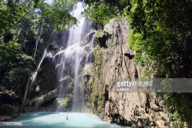 touristen genießen einen wunderschönen wasserfall - cebu stock-fotos und bilder