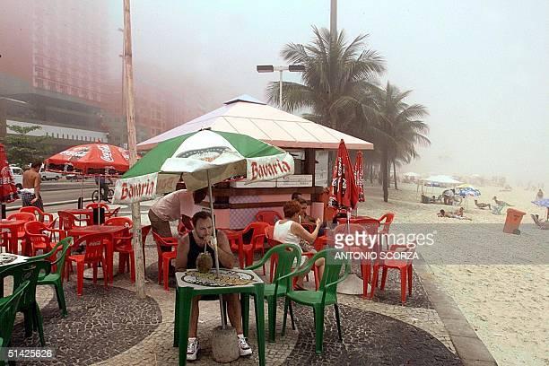 Tourists enjoy a beverage at a kiosk next to the Copacabana beach in Rio de Janerio, Brazil 09 December 1999. Turistas disfrutan de una bebida en un...