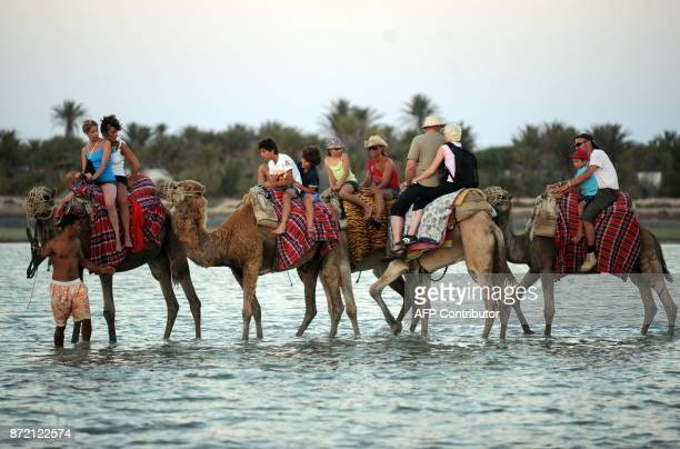Tourists enjoy a camel ride during their hollidays in Djerba on August 1 2010 AFP PHOTO / FETHI BELAID / AFP PHOTO / Fethi Belaid