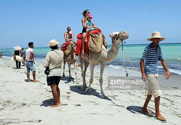Tourists enjoy a camel ride on the pink flamingo Island beach on August 2 2010 near Djerba AFP PHOTO / FETHI BELAID