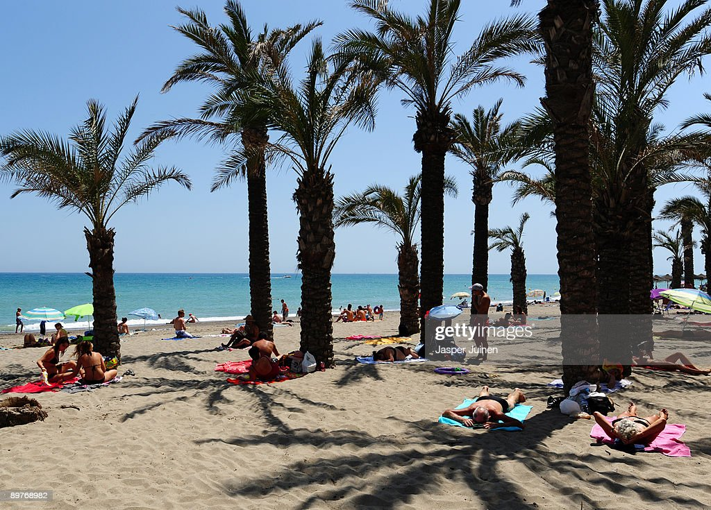 Tourists enjoy a clear blue sky amid palm trees at a usually packed Costa del Sol Carihuela beach on August 12, 2009 in Torremolinos, Spain. Altough Spanish resorts remain busy, receiving 23.6 million foreign visitors in the first half year, the economic downturn has seen more than an eleven percent drop in visitors, especially from Britain, over the same period as last year. European holidaymakers are increasingly staying at home for their annual holidays.