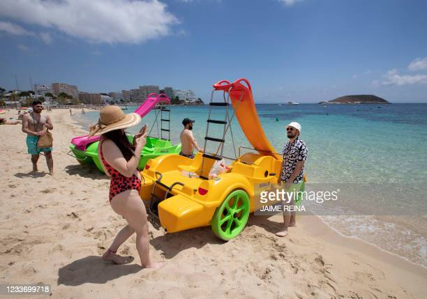 Tourists enjoy a day at Magaluf Beach in Calvia, on the Balearic Island of Mallorca, on June 28, 2021. - British holidaymakers heading to the...