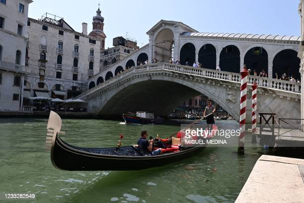 Tourists enjoy a gondola ride by the Rialto bridge on the Grand Canal in Venice on June 05, 2021.