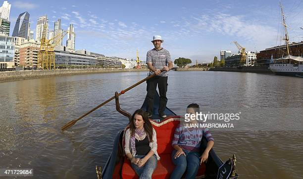 Tourists enjoy a ride in a Venetian gondola through Puerto Madero in Buenos Aires on April 30 2015 AFP PHOTO / JUAN MABROMATA