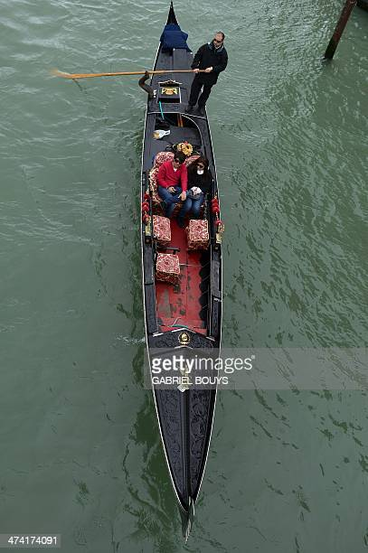 Tourists enjoy a ride on a gondola in spite of the rain on February 22 2014 in Venice The 2014 edition of the Venice carnival entitled 'Wonder and...
