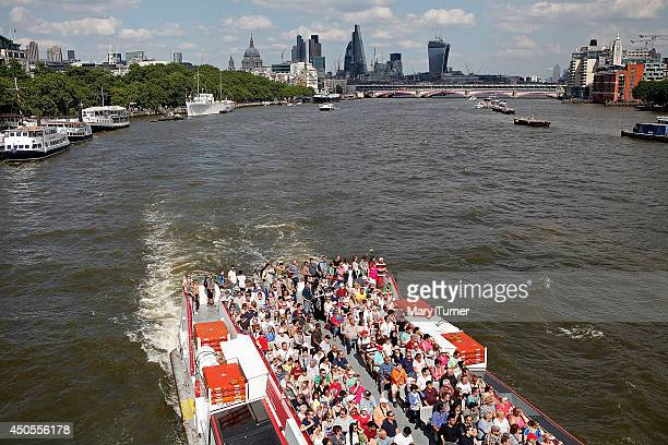 Tourists enjoy a riverboat cruise in the sunshine on the River Thames as forecasters predict that it will be the hottest day of the year on June 13...