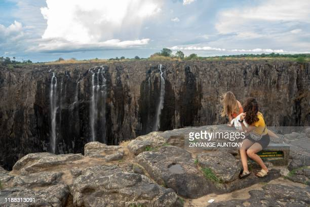 Tourists enjoy a serene time as they look on trickles of water at the Victoria Falls on December 10 2019 The Victoria Falls a UNESCO world heritage...