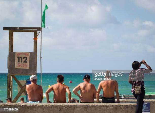 Tourists enjoy a sunny day at the Playa de Palma beach in Palma de Mallorca on September 24 2019 Britain has repatriated ten percent of nationals who...