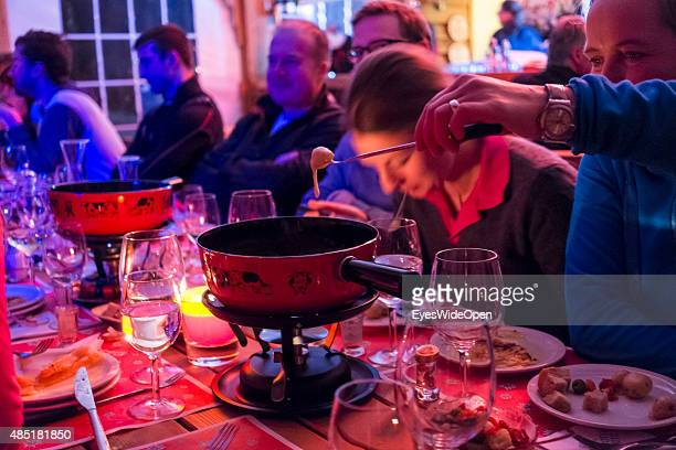 Tourists enjoy a traditional cheese fondue in a hut at the ski area Piz Corvatch on December 14 2013 in St Moritz EngadinGraubunden Switzerland