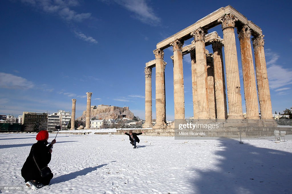Tourists enjoy a view of the archaeological site of the ancient Temple of Zeus with the Acropolis Hill behind which are covered in snow on January 10, 2017 in Athens, Greece. Schools in Athens remained closed on Tuesday and the rare snowfall caused traffic disruptions in the city centre.