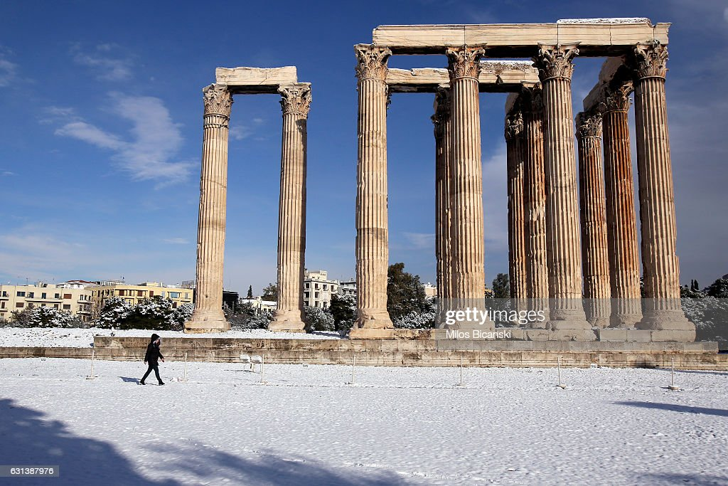 Tourists enjoy a view of the archaeological site of the ancient Temple of Zeus which is covered in snow on January 10, 2017 in Athens, Greece. Schools in Athens remained closed on Tuesday and the rare snowfall caused traffic disruptions in the city centre.