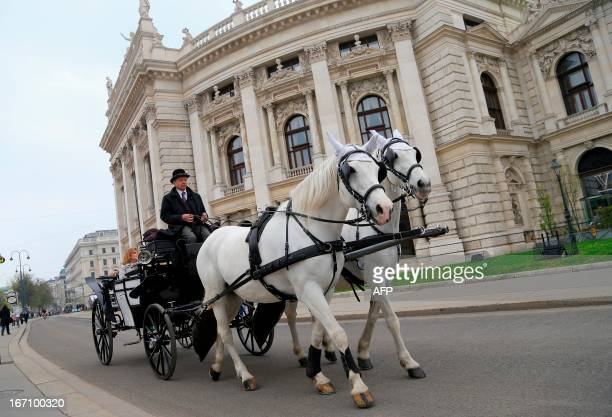 Tourists enjoy a visit of the city in a fiaker horsedrawn carriage in Vienna on April 20 2013 AFP PHOTO / ALEXANDER KLEIN / AFP PHOTO / ALEXANDER...
