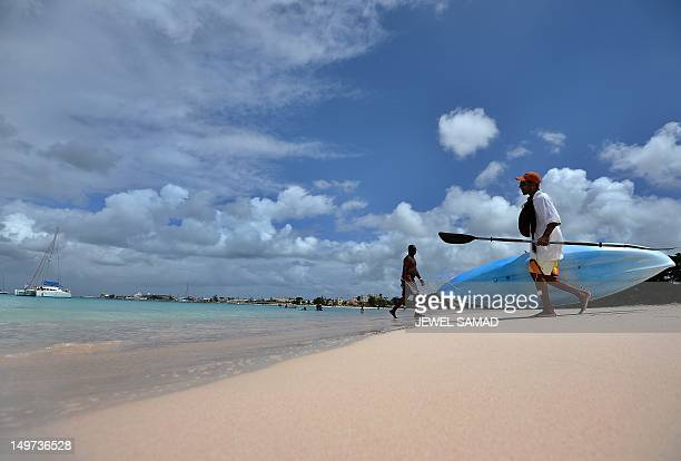 Tourists enjoy at a beach in Bridgetown on April 12 2012 Historically the economy of Barbados had been dependent on sugarcane cultivation and related...