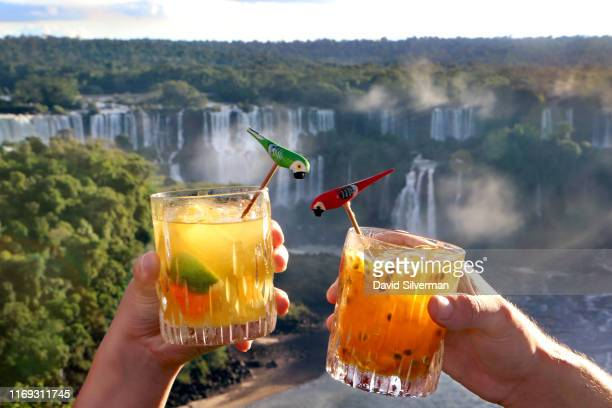Tourists enjoy Brazilian Caipirinha cocktails, made with Cachaca, fruit and sugar, in front of the evening panoramic view of the Argentinian side of...