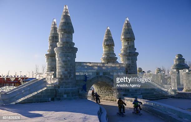 Tourists enjoy ice track cycling as they ride through an ice castle during the 33rd Harbin International Ice and Snow Festival at Harbin Ice And Snow...