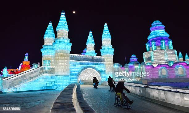 Tourists enjoy ice track cycling as they ride through an illuminated ice castle during the 33rd Harbin International Ice and Snow Festival at Harbin...