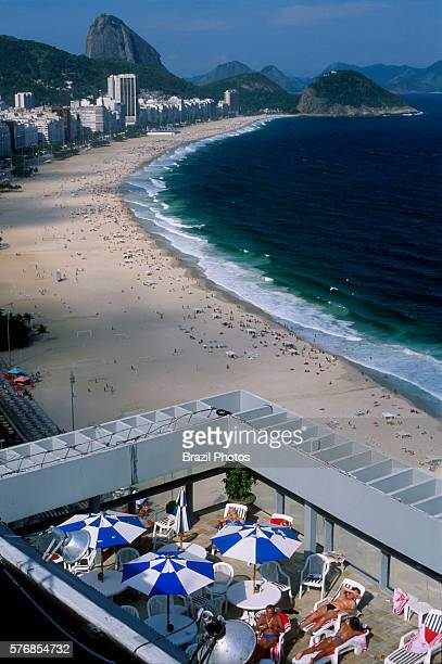 Tourists enjoy Rio Othon Palace Hotel swimming pool view of Copacabana beach and Sugar Loaf mountain Rio de Janeiro Brazil