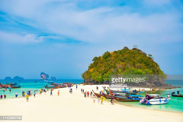 Tourists enjoy sightseeing turquoise sea and small white sand beach at Talay Waek between Koh Tup and Koh Mor Island in Summe bule Sky Day