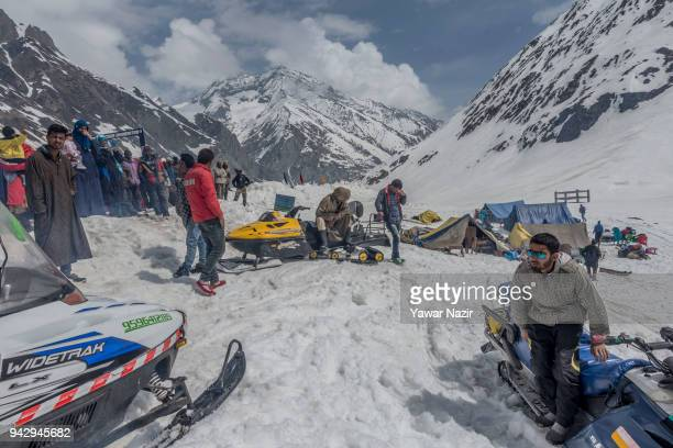 Tourists enjoy snow scooter ride on the snow clad mountains after the SrinagarLeh highway was opened on April 6 2018 in Zojila 108 km east of...