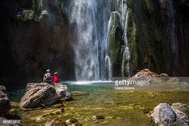 Tourists enjoy sunny day as water falls down from the Big Waterfall at Plitvice Lakes National Park on July 6 2015 near Plitvicka Jezera Croatia...