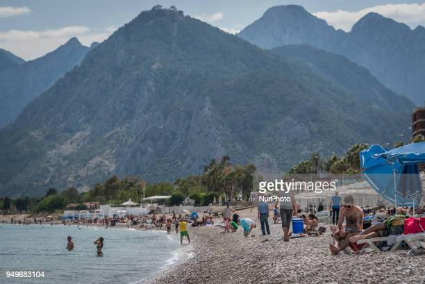 Tourists enjoy sunshine mountain landscapes and clear blue Mediterranean waters on the beaches of Antalya a tourism hub on the southern coast of...