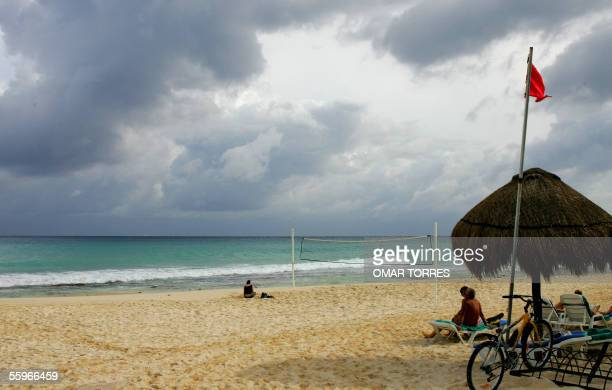 Tourists enjoy the beach 19 October 2005 at Playa del Carmen some 50 kilometers from Cancun Mexico whilst category five storm Wilma approaches the...