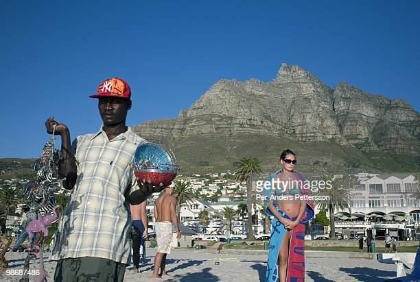 Tourists enjoy the beach as the sun sets on March 21 2009 in Camps Bay a posh sea side resort in Cape Town South Africa Camps Bay is one of the most...
